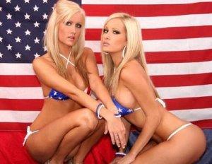Half naked ladies wearing patriotic bikinis in front of the American flag